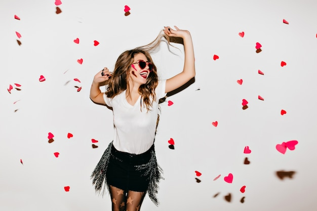 Élégante jeune femme en lunettes de soleil à la mode regardant les cœurs tombés