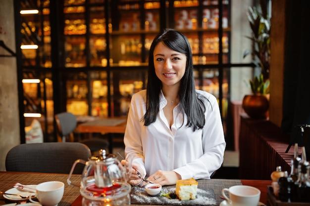 Élégante jeune femme mangeant un dessert dans un restaurant