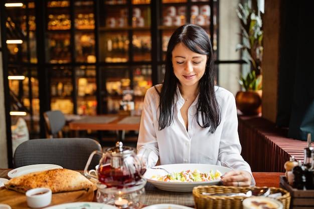 Élégante jeune femme mangeant de la salade dans un restaurant