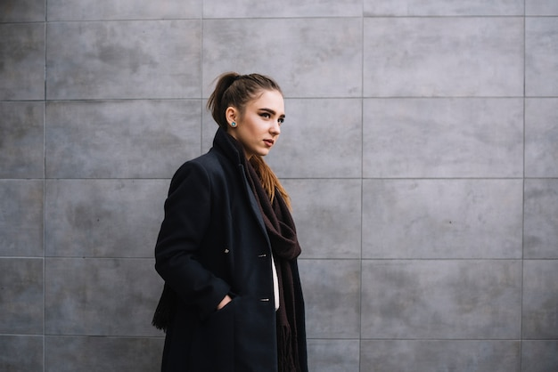 Élégante jeune femme en manteau avec écharpe près du mur gris