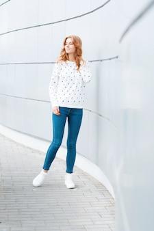 Élégante jeune femme mince européenne dans un pull vintage en jean bleu à la mode en baskets blanches à la mode à l'intérieur près du mur