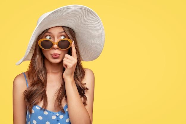 Élégante jeune femme portant un chapeau posant contre le mur jaune