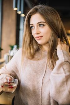 Élégante jeune femme positive avec une tasse de café