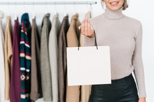 Élégante jeune femme en pull gris clair et pantalon en cuir noir tenant un sac en papier blanc