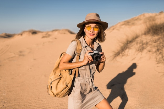 Élégante jeune femme en robe kaki marchant dans le désert, voyageant en afrique en safari, portant un chapeau et un sac à dos, prenant une photo sur un appareil photo vintage