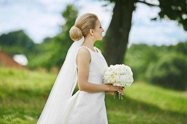 Élégante jeune femme en robe de mariée élégante avec bouquet de fleurs blanches dans ses mains posant à l'extérieur