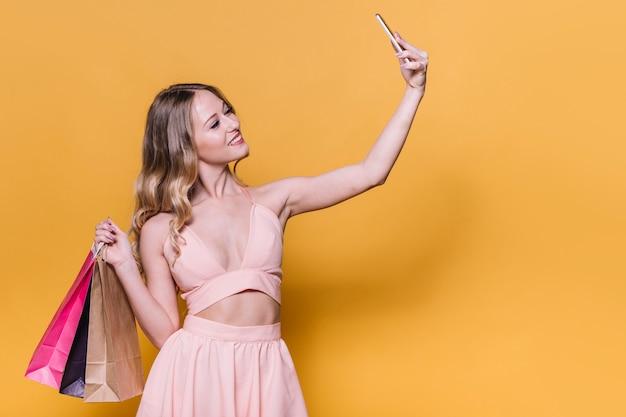 Élégante jeune femme avec des sacs prenant selfie