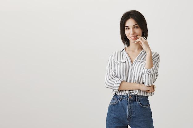 Élégante jeune femme souriante avec une expression réfléchie