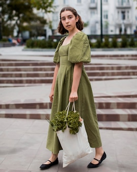 Élégante jeune femme transportant un sac d'épicerie