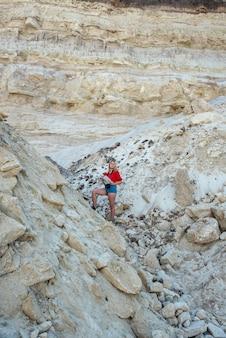 Élégante jeune femme traverse des canyons et des rochers de sable pour prendre des photos et profiter des vacances d'été