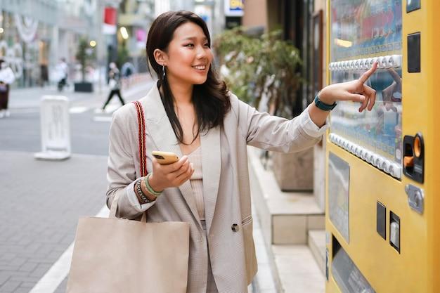 Élégante jeune femme vérifiant le distributeur automatique