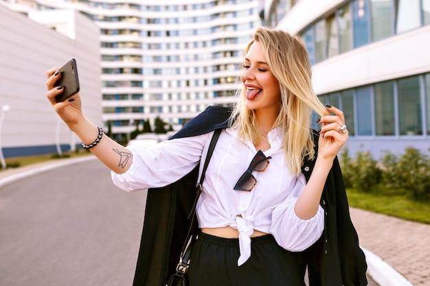 Élégante jeune femme vêtue d'un costume bleu marine à la mode, posant près de bâtiments modernes, accessoires à la mode, faisant selfie et montrant la langue, humeur positive.