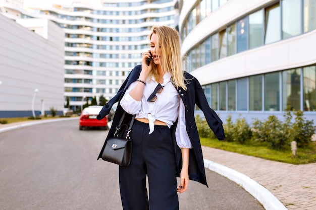 Élégante jeune femme vêtue d'un costume bleu marine à la mode, posant près de bâtiments modernes, d'accessoires à la mode, parlant par son téléphone, a quitté les émotions.