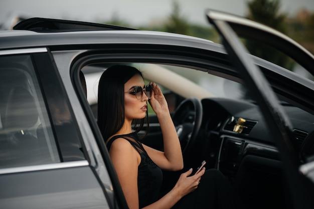 Élégante jeune fille assise dans une voiture de classe affaires dans une robe noire. mode et style d'entreprise