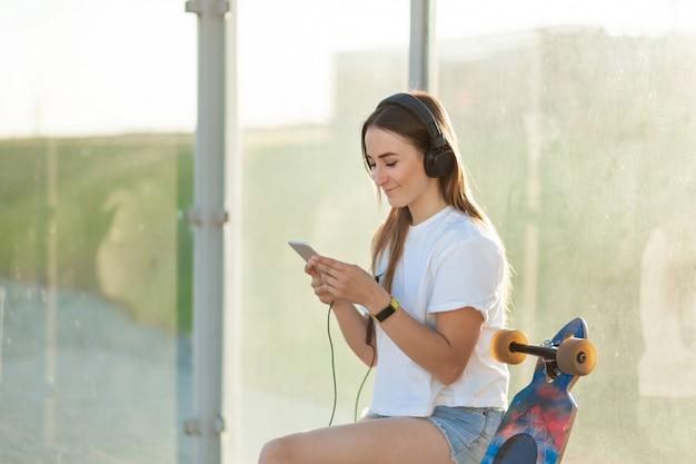 Élégante jeune fille assise avec son longboard et écoute de la musique