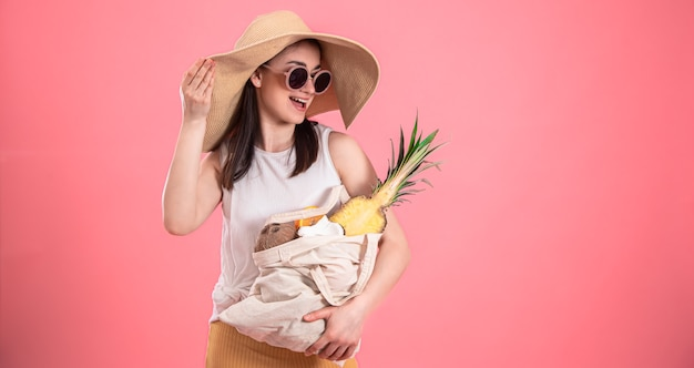 Élégante jeune fille au grand chapeau et lunettes de soleil sourit et tient un sac écologique avec des fruits exotiques
