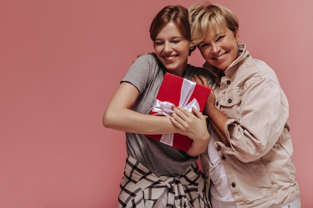 Élégante jeune fille de bonne humeur aux cheveux courts brune tenant une boîte-cadeau, souriant et posant avec une femme aux cheveux blonds sur fond rose.