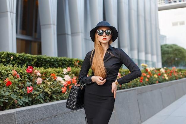Élégante jeune fille dans un chapeau et des vêtements noirs avec des lunettes de soleil