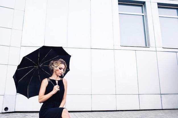 Élégante jeune fille dans une robe noire et avec un parapluie posant contre un mur gris.