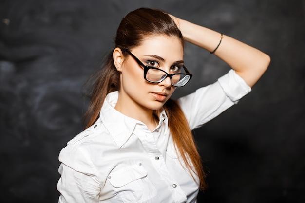 Élégante jeune fille étudiante dans un chemisier blanc et des lunettes
