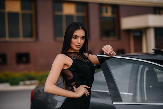 Élégante jeune fille se tient près de la voiture dans une robe noire. mode et style d'entreprise.