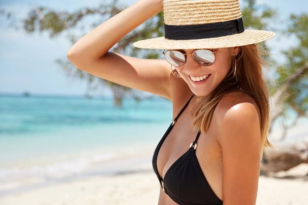 Élégante jeune mannequin détendue en maillot de bain noir, porte des lunettes de soleil à la mode et un chapeau de paille, pose contre une belle vue marine, a un regard heureux vers le bas. concept de personnes, repos d'été et tourisme