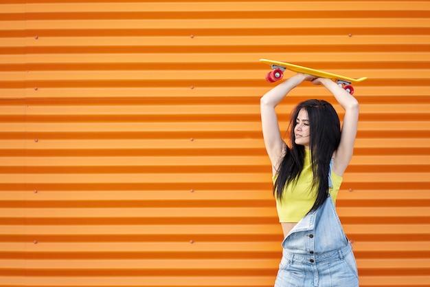 Élégante jolie femme brune aux cheveux longs portant un haut jaune et une salopette en jean bleu.