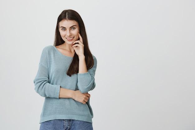 Élégante jolie femme brune souriant à la caméra