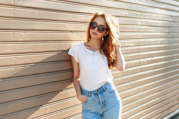 Élégante jolie femme hipster à lunettes de soleil et jeans taille haute vintage appuyé contre le mur en bois