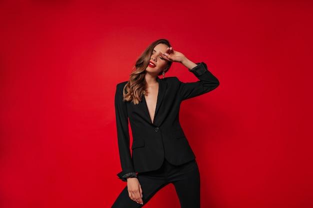 Élégante jolie femme vêtue d'un costume noir posant sur un mur rouge