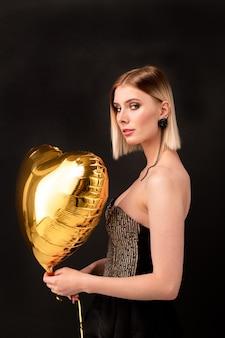 Élégante jolie fille avec ballon en forme de coeur de couleur dorée vous regarde tout en profitant de la fête de la saint-valentin dans la boîte de nuit
