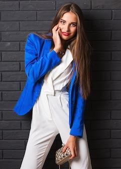 Élégante jolie jeune femme en costume blanc décontracté et veste bleue tenant un sac à main de luxe