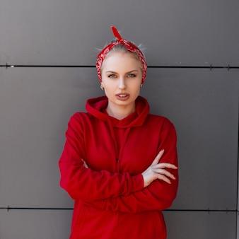 Élégante jolie jeune femme dans des vêtements à la mode modernes avec un bandana rouge est debout près d'un bâtiment moderne gris sur une chaude journée d'été