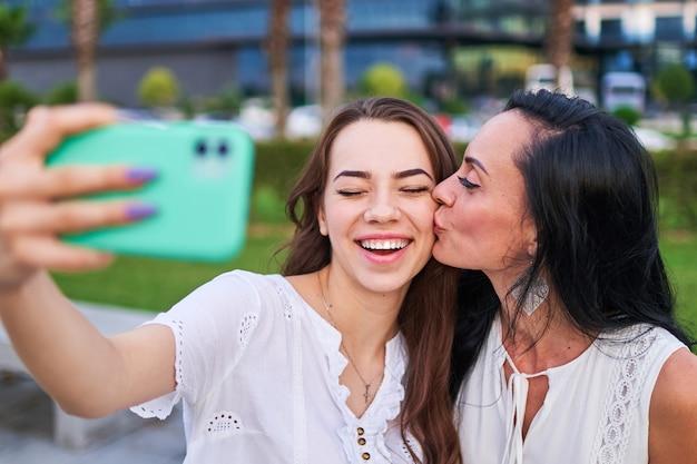 Élégante jolie mère embrasse sur la joue sa joyeuse fille heureuse et prend selfie photo portrait sur l'appareil photo du téléphone tout en marchant ensemble à l'extérieur