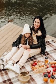 Élégante maman et sa fille au pique-nique d'automne s'asseoir sur une couverture près de l'eau