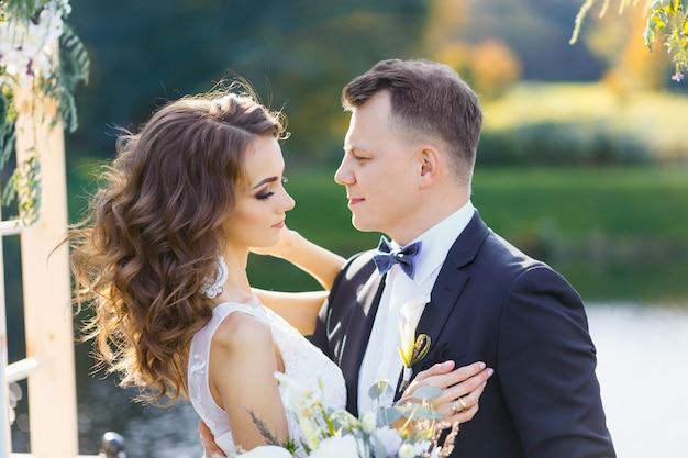Élégante mariée bouclée et heureux marié à l'extérieur sur le fond du lac. cérémonie de mariage élégante et créative
