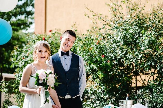 Élégante mariée heureuse avec un bouquet de pivoines et le marié se tiennent la main