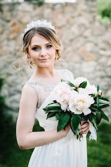 Élégante mariée sourire heureux avec bouquet de pivoines avec couronne pose sur la surface dans la cour