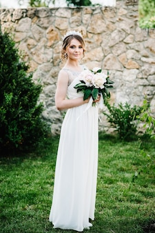 Élégante mariée sourire heureux avec bouquet de pivoines avec couronne, stand, pose sur l'herbe sur la surface dans la cour