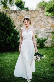 Élégante mariée sourire heureux avec bouquet de pivoines avec couronne, va sur l'herbe sur la surface dans la cour