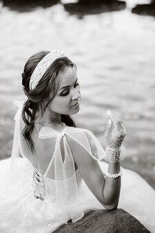 Une élégante mariée vêtue d'une robe blanche, de gants et de pieds nus est assise près d'une cascade dans le parc, profitant de la nature.un modèle en robe de mariée et des gants dans un parc naturel.biélorussie. photo en noir et blanc