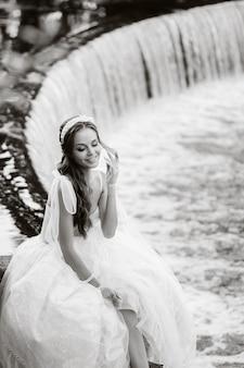 Une élégante mariée vêtue d'une robe blanche, de gants et de pieds nus est assise près d'une cascade dans le parc, profitant de la nature.un modèle en robe de mariée et des gants dans un parc naturel.biélorussie