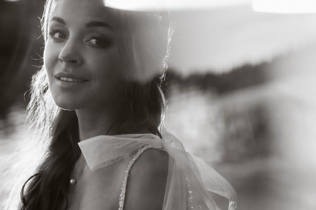 Une élégante mariée vêtue d'une robe blanche profite de la nature au coucher du soleil.modèle en robe de mariée dans la nature dans le parc.biélorussie. photo en noir et blanc