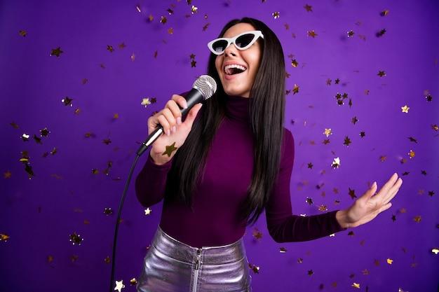 Élégante petite amie décontractée à la mode chantant dans le microphone appréciant son être au bar karaoké isolé mur de couleur vive violet