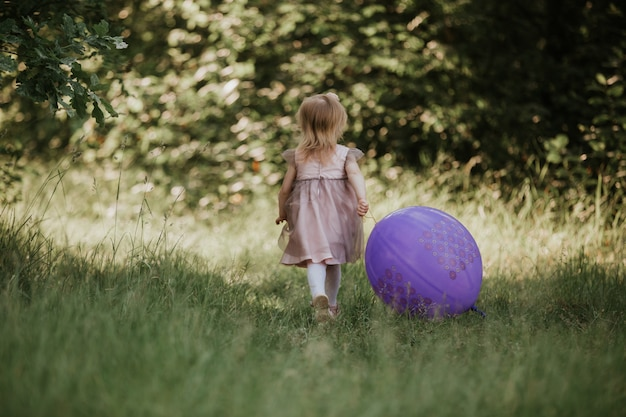 Élégante petite fille 2-5 ans tenant le gros ballon vêtue d'une robe rose tendance dans prairie. espiègle. fête d'anniversaire. petite fille avec un ballon dans le parc