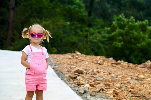 Élégante petite fille aux cheveux blonds debout en plein air
