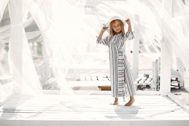Élégante petite fille sur une côte d'été