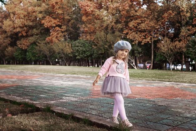 Élégante petite fille marchant dans un parc automnal