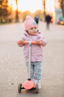 Élégante petite fille monte un scooter dans le parc au coucher du soleil
