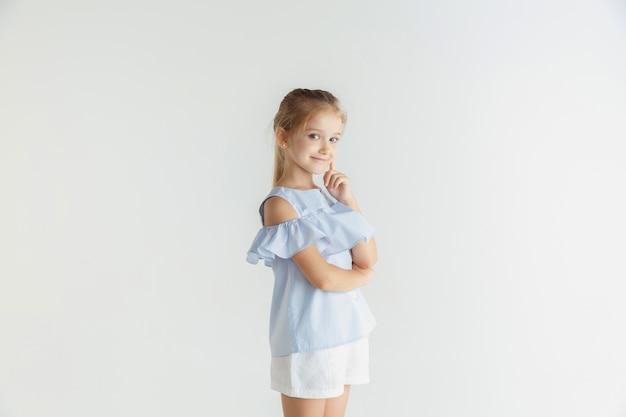 Élégante petite fille souriante posant dans des vêtements décontractés isolé sur studio blanc